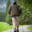 Active handsome senior man nordic walking outdoors on a forest p — Stok fotoğraf