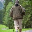 Active handsome senior man nordic walking outdoors on a forest p - 图库照片