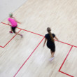 Two female squash players in fast action on a squash court (moti — Stockfoto