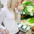 Stock Photo: Beautiful young woman shopping for fruits and vegetables in prod