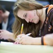 Pretty female college student sitting an exam in a classroom ful — Stock Photo #6149997