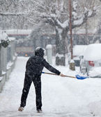 Woman shoveling snow from a sidewalk after a heavy snowfall in a — Stock Photo