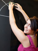Pretty young college student drawing on the chalkboard/blackboar — Stock Photo