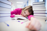 In the library - very tired/exhausted, pretty, female student wi — Stock Photo