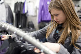Pretty teenager shopping for clothes in a boutique/fashion shop/ — ストック写真