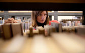 Pretty female college student in a llibrary — Foto de Stock