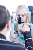Optometry concept - pretty young female patient having her eyes — Stock Photo