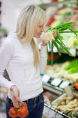 Beautiful young woman shopping for fruits and vegetables in prod — Stock Photo