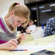 Stock Photo: Pretty female college student sitting exam in classroom ful