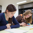 Pretty female college student sitting an exam in a classroom ful — Stockfoto