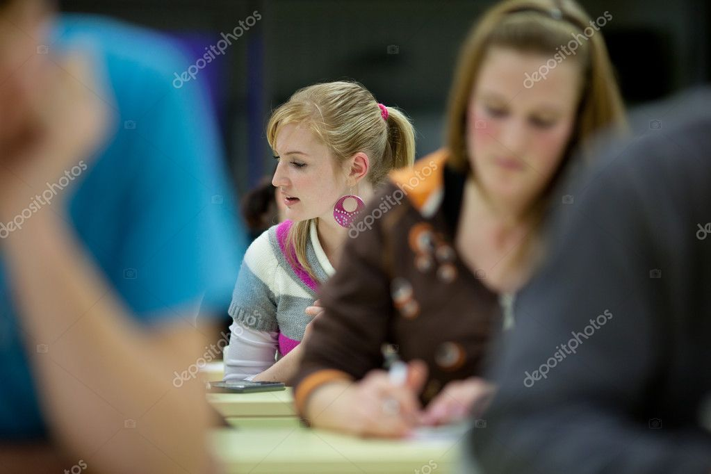 Pretty female college student sitting in a classroom full of students during class (shallow DOF; color toned image) — Lizenzfreies Foto #6150002