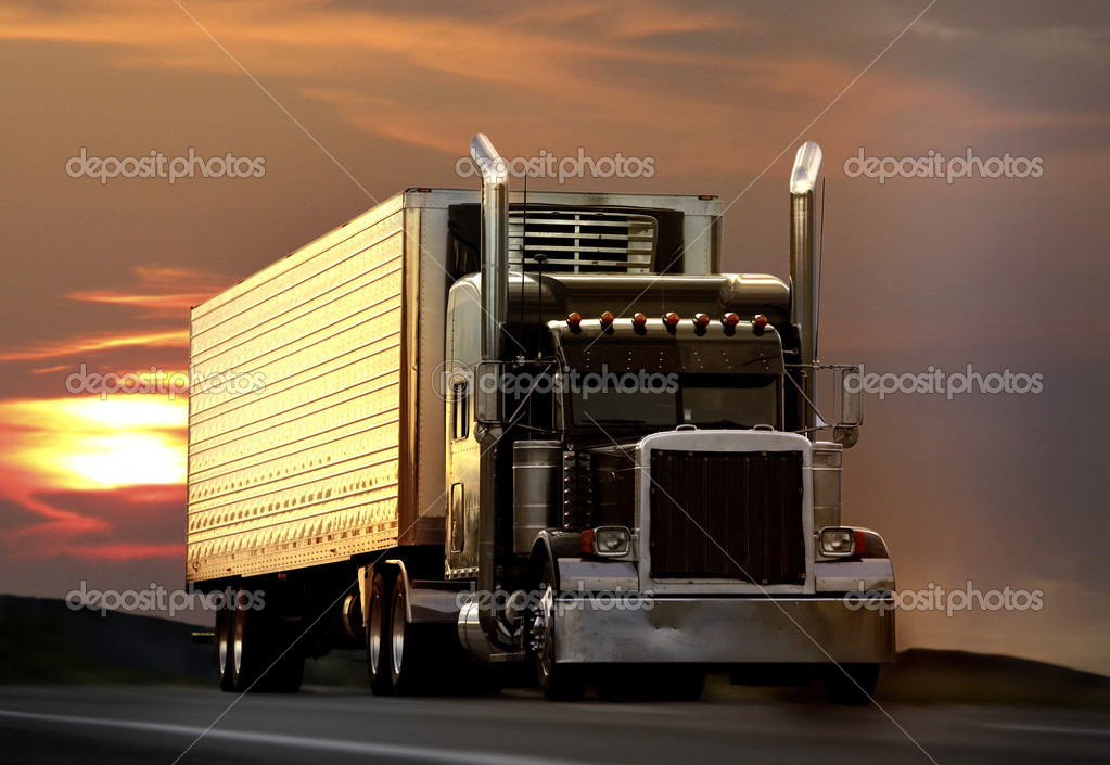 Big truck driving on a highway with sunset in background — Stock Photo #5526070