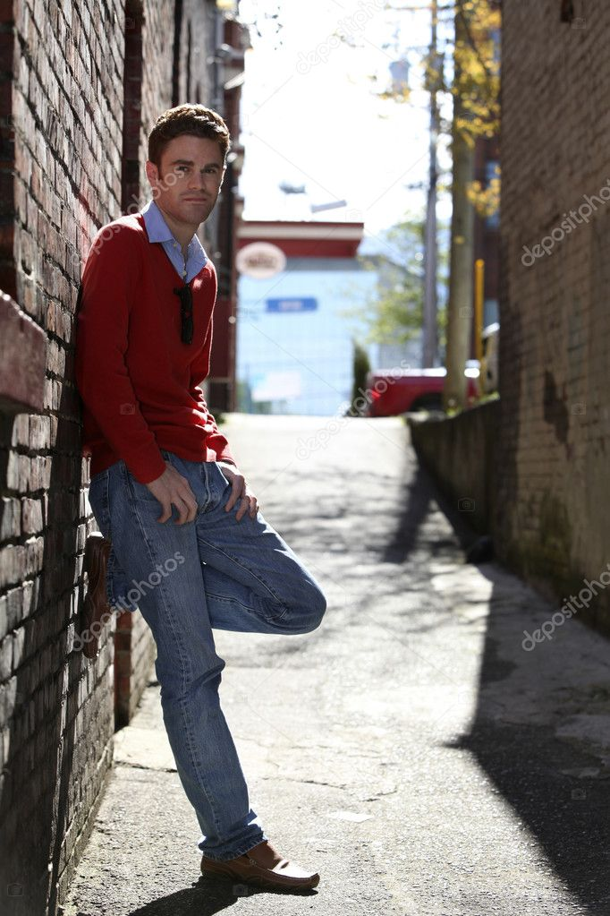 Portrait of a young man leaning on a brick wall — Stock Photo #5667788