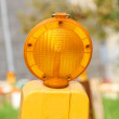 Conspicuous yellow warning road flashlight - Stock Photo
