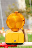 Conspicuous yellow warning road flashlight — Stock Photo