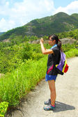Young woman with backpack hiking and taking a photo — Stock Photo