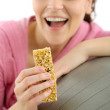 Fitness woman eat granola sportive outfit happy — Stock Photo #5555842