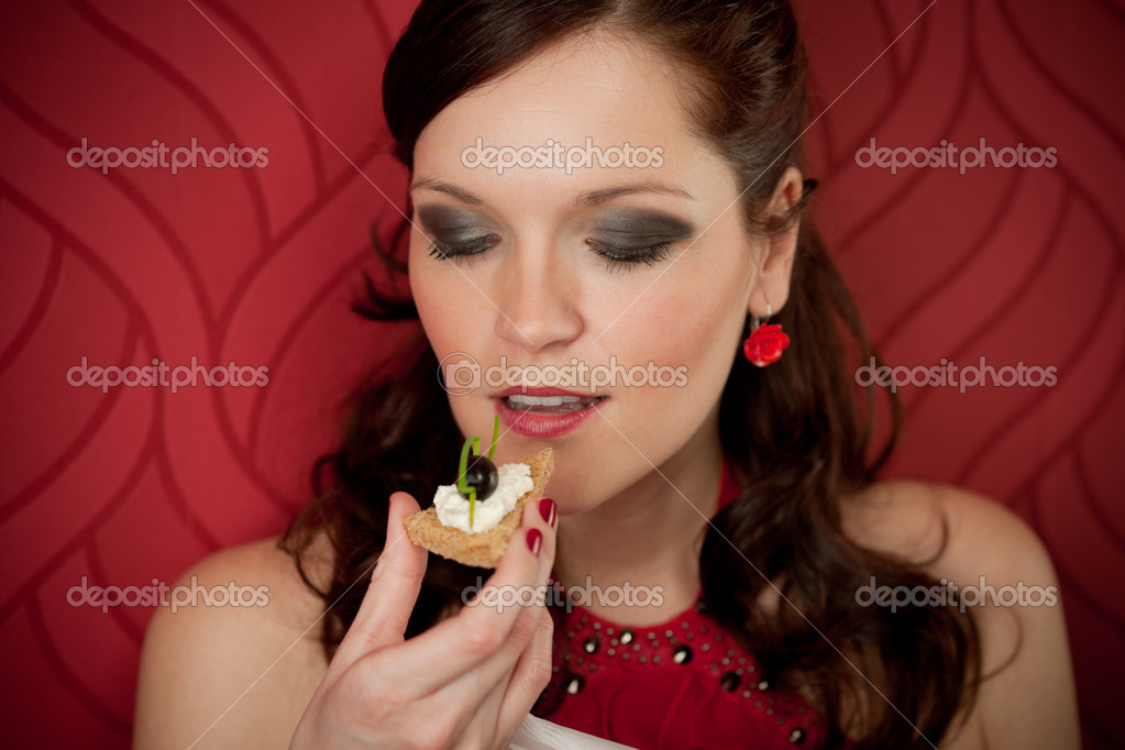 Cocktail party woman eat appetizer evening dress red background — Stock Photo #5555859
