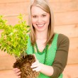 Stock Photo: Portrait happy woman hold plant spring gardening