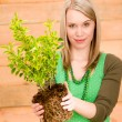 Portrait happy woman hold plant spring gardening — Stock Photo
