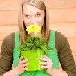 Portrait happy woman smell yellow spring flower — Stock Photo