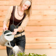 Gardening woman watering plant spring terrace - Stock Photo
