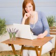 Summer terrace redhead woman with laptop — Stock Photo