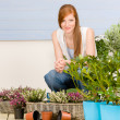 Summer garden terrace redhead woman with flowers — Stock Photo