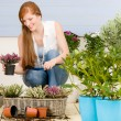 Summer garden terrace redhead woman with flowers — Stock Photo #5572957