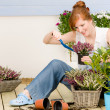 Summer garden terrace redhead woman potted flower — Stock Photo #5572966