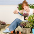 Summer garden terrace redhead woman potted flower - Foto de Stock  