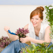Summer garden terrace redhead woman potted flower — Stock Photo