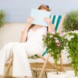 Summer terrace red hair woman read in deckchair — Stock Photo