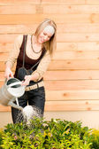 Gardening woman watering plant spring terrace — Stock Photo
