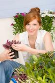 Summer garden terrace redhead woman potted flower — Stock Photo