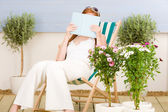 Summer terrace red hair woman read in deckchair — Foto Stock