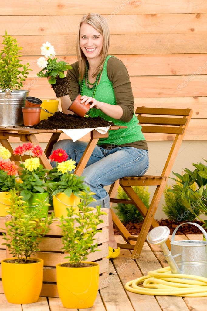 Gardening woman planting spring flower on terrace  Stock Photo #5572783