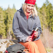 Active woman rock climbing with thermosbottle — Stock Photo
