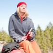 Active woman rock climbing relax with thermobottle — Stock Photo