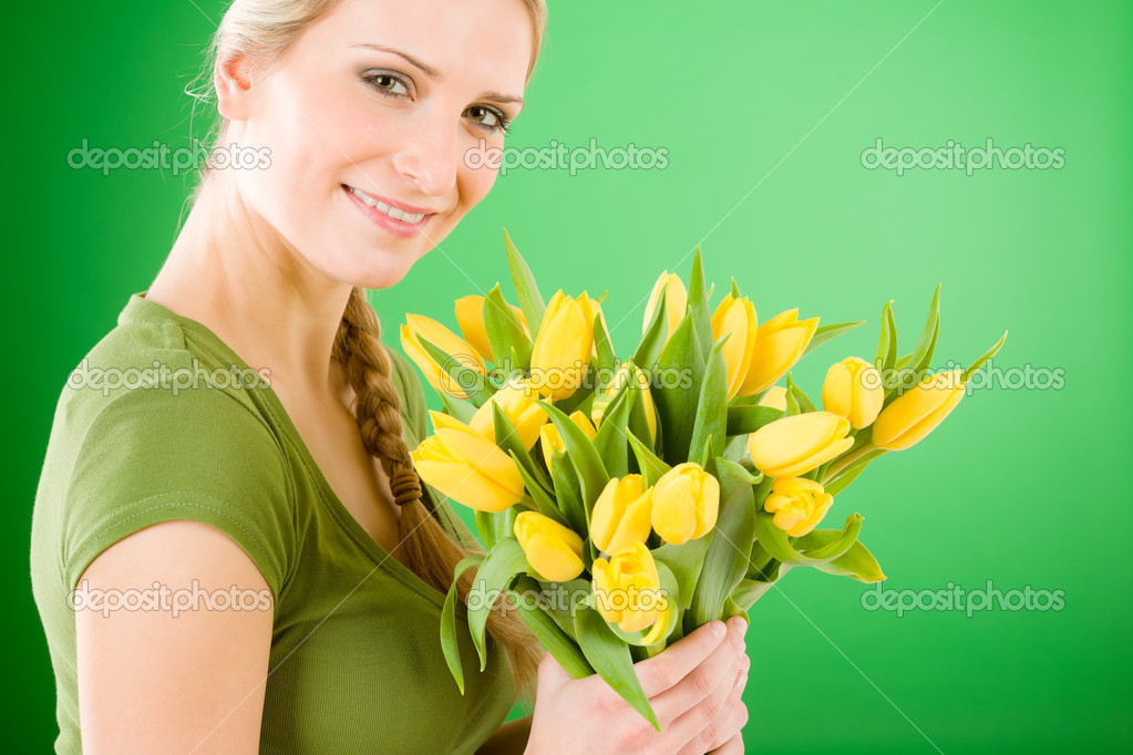 Young blond woman hold yellow tulips flower on green — Stock Photo #5657345