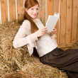 Young romantic woman read book in barn — Стоковая фотография