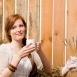 Young romantic woman in barn holding cup — Stok fotoğraf