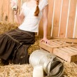 Young healthy woman hold glass of milk in barn — Stock Photo