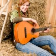 Young country woman with guitar in barn — Stock Photo