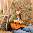 Young country woman play guitar in barn — Stock Photo #5757140