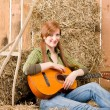 Young country woman play guitar in barn — Stock Photo