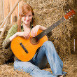 Young country woman sitting on hay with guitar — Stock Photo #5757142