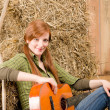 Stock Photo: Young country woman playing guitar in barn
