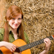 Young country woman playing guitar in barn - Stock Photo