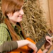 Young country woman playing guitar in barn — Stock Photo #5757157